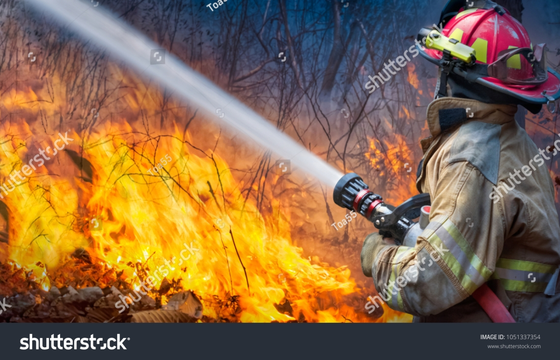 stock-photo-natural-disaster-firefighters-spray-water-to-wildfire-1051337354